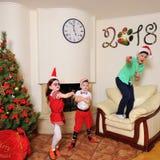 Καλό νέο πνεύμα έτους: Χριστουγεννιάτικο δέντρο, τσάντα δώρων, εστία και διακόσμηση Santa και δύο παιδιά Στοκ φωτογραφία με δικαίωμα ελεύθερης χρήσης