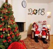 Καλό νέο πνεύμα έτους: Χριστουγεννιάτικο δέντρο, τσάντα δώρων, εστία και διακόσμηση Santa και δύο παιδιά Στοκ Εικόνα