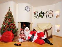 Καλό νέο πνεύμα έτους: Χριστουγεννιάτικο δέντρο, τσάντα δώρων, εστία και διακόσμηση για το έτος του σκυλιού Santa και ένα κορίτσι Στοκ Φωτογραφίες