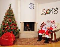 Καλό νέο πνεύμα έτους: Χριστουγεννιάτικο δέντρο, τσάντα δώρων, εστία και διακόσμηση Santa και δύο παιδιά Στοκ Εικόνες