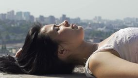 Καλό να βρεθεί γυναικών της άκρης της στέγης που απολαμβάνει τον ήλιο, γραμμή ουρανού πόλεων στο υπόβαθρο απόθεμα βίντεο