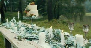Καλό ντεκόρ για το ρομαντικό γεύμα στο misty δασικό επιτραπέζιο σύνολο των φύλλων, των κεριών, των λουλουδιών και του άσπρου νόστ απόθεμα βίντεο