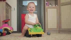 Καλό παιχνίδι αγοράκι με ένα μεγάλο παιχνίδι αυτοκινήτων στο πάτωμα στο σπίτι Παιχνίδι μικρών παιδιών αγοριών παιδιών με το αυτοκ απόθεμα βίντεο