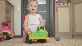 Καλό παιχνίδι αγοράκι με ένα μεγάλο παιχνίδι αυτοκινήτων στο πάτωμα στο σπίτι Παιχνίδι μικρών παιδιών αγοριών παιδιών με το αυτοκ φιλμ μικρού μήκους