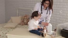 Καλό παιχνίδι γιατρών γυναικών με ένα κορίτσι, υποδοχή στο γιατρό των παιδιών φιλμ μικρού μήκους