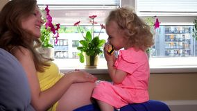 Καλό παιχνίδι κοριτσιών παιδιών με τη συνεδρίαση στοματικών οργάνων στα έγκυα γόνατα μητέρων απόθεμα βίντεο