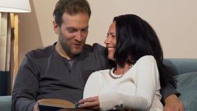 Καλό παντρεμένο ώριμο ζευγάρι που γελά διαβάζοντας ένα βιβλίο από κοινού απόθεμα βίντεο