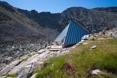 Καλύβα καταφυγίων έκτακτης ανάγκης κατά μήκος ενός ίχνους πεζοπορίας στο βουνό στοκ φωτογραφία