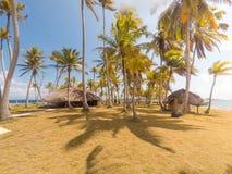 Καλύβες/μπανγκαλόου Thatch στο μικρό τροπικό νησί με τους φοίνικες στοκ φωτογραφία