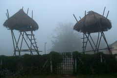 Καλύβες των κυνηγών και των φυλάκων κοντά στον ξύλινο φράκτη, μπανγκαλόου στα υψηλά ξυλοπόδαρα, λυκόφως και ομίχλη Στοκ Εικόνες