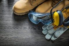 Καλύμματα αυτιών προστατευτικών διόπτρων μποτών γαντιών ασφάλειας στον ξύλινο πίνακα Στοκ εικόνες με δικαίωμα ελεύθερης χρήσης