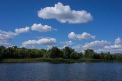 Καλύπτει κοντά στην όχθη ποταμού Χνουδωτά σύννεφα πέρα από τον ποταμό στοκ φωτογραφίες