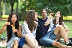 Καλύτεροι φίλοι που στηρίζονται στο πάρκο και τις φυσώντας φυσαλίδες σαπουνιών Στοκ Φωτογραφίες