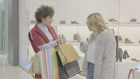 Καλύτεροι φίλοι στις φέρνοντας τσάντες αγορών λεωφόρων και παρουσίαση ο ένας στον άλλο τι αγόρασαν από τα καταστήματα εμπορικών σ απόθεμα βίντεο