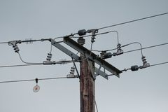 Καλώδια και μονωτές ηλεκτρικής δύναμης υψηλής τάσης που βλέπουν στους ξύλινους πόλους στοκ εικόνα