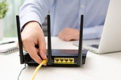 Καλώδιο Ethernet βουλωμάτων ατόμων στο δρομολογητή Στοκ φωτογραφίες με δικαίωμα ελεύθερης χρήσης