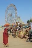Καμήλες γυναικών και ρόδες ferris στην έκθεση καμηλών Pushkar Στοκ Εικόνες