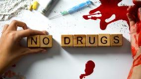 Καμία λέξη φαρμάκων σε ετοιμότητα τους ξύλινους κύβους, αιμορραγώντας και τα ναρκωτικά στον πίνακα, έννοια στοκ εικόνες