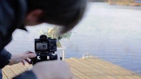Καμεραμάν με τη κάμερα στην ανθοδέσμη πυροβολισμού τρίποδων φιλμ μικρού μήκους