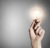 καμμένος γκρίζο χέρι ανασκόπησης lightbulb Στοκ Εικόνες