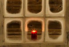Καμμένος κόκκινο κερί στο χιονισμένο παράθυρο Στοκ εικόνες με δικαίωμα ελεύθερης χρήσης
