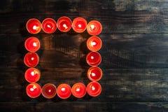 Καμμένος μικρά κόκκινα κεριά που τακτοποιούνται στο τετράγωνο Στοκ φωτογραφίες με δικαίωμα ελεύθερης χρήσης