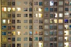 Καμμένος παράθυρα διαμερισμάτων τη νύχτα όπου κάθε κάτοχος έχει τη μυστικότητά του στην καλά προγραμματισμένη υψηλή άνοδο Ηλεκτρι Στοκ Εικόνα