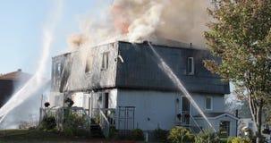 Καμμένος πυρκαγιά σπιτιών Οι πυροσβέστες ψεκάζουν το νερό στο σπίτι με τη μάνικα απόθεμα βίντεο