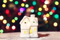 Καμμένος σπίτι παιχνιδιών Χριστουγέννων σε ένα υπόβαθρο της γιρλάντας ενός νέου έτους στοκ φωτογραφίες