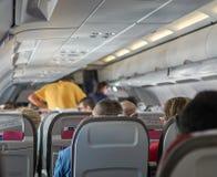 Καμπίνα αεροπλάνων οικονομικής θέσης με το μόνιμες άτομο και την αεροσυνοδό στοκ εικόνες με δικαίωμα ελεύθερης χρήσης