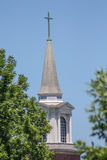 Καμπαναριό εκκλησιών ενάντια στο μπλε ουρανό με τα πράσινα δέντρα Στοκ εικόνες με δικαίωμα ελεύθερης χρήσης