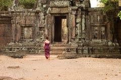 Καμποτζιανό κορίτσι στους Khmer περιπάτους φορεμάτων προς την πόρτα ενός τοίχου σε Angkor Thom Στοκ Φωτογραφίες