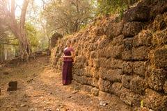 Καμποτζιανό κορίτσι στο Khmer φόρεμα από έναν αρχαίο τοίχο και δέντρο σε Angkor Thom, πόλη Angkor Στοκ Εικόνα