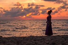 Καμποτζιανό κορίτσι στο Khmer φόρεμα που προσέχει το ηλιοβασίλεμα στην παραλία Στοκ Εικόνα
