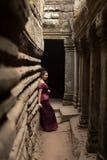 Καμποτζιανό κορίτσι στο Khmer φόρεμα που στέκεται στο ναό Bayon στην πόλη Angkor Στοκ εικόνα με δικαίωμα ελεύθερης χρήσης