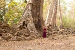 Καμποτζιανό κορίτσι στο Khmer φόρεμα που υπερασπίζεται ένα παλαιό δέντρο σε Angkor Thom Στοκ Φωτογραφία