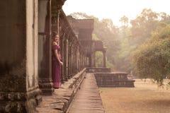 Καμποτζιανό κορίτσι στο Khmer φόρεμα που υπερασπίζεται τους στυλοβάτες Angkor Wat στοκ φωτογραφία με δικαίωμα ελεύθερης χρήσης