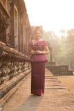 Καμποτζιανό κορίτσι στο Khmer φόρεμα που υπερασπίζεται τους στυλοβάτες Angkor Wat Στοκ Φωτογραφίες