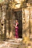 Καμποτζιανό κορίτσι στο Khmer φόρεμα στην πόρτα του αρχαίου κτηρίου Στοκ φωτογραφίες με δικαίωμα ελεύθερης χρήσης
