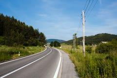 Καμπύλη της εθνικής οδού που περιβάλλεται με τις δασικές πράσινες στήλες τομέων και ηλεκτρικής δύναμης στα βουνά στην Κροατία Στοκ Εικόνες