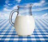 Κανάτα γάλακτος στον μπλε πίνακα στοκ εικόνες