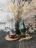 Κανάτα γυαλιού και φλυτζάνι του τσαγιού στον ξύλινο πίνακα στοκ εικόνες