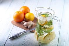 Κανάτα γυαλιού του νερού, των πορτοκαλιών, του λεμονιού και της πιπερόριζας detox Στοκ Εικόνες