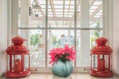 Κανάτα των φρέσκων θερινών λουλουδιών και των λαμπτήρων σε μια στρωματοειδή φλέβα παραθύρων στοκ φωτογραφία