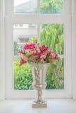 Κανάτα των φρέσκων θερινών λουλουδιών σε μια στρωματοειδή φλέβα παραθύρων στοκ φωτογραφίες