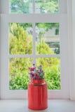 Κανάτα των φρέσκων θερινών λουλουδιών σε μια στρωματοειδή φλέβα παραθύρων στοκ φωτογραφία
