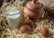 Κανάτες αργίλου, αυγά, ποτήρι του γάλακτος, στο άχυρο και burlap Στοκ εικόνα με δικαίωμα ελεύθερης χρήσης