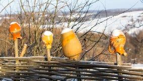 Κανάτες αργίλου στον ξύλινο φράκτη το χειμώνα Στοκ Εικόνες