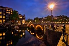Κανάλι Amterdam, γέφυρα και μεσαιωνικά σπίτια το βράδυ Στοκ Εικόνα