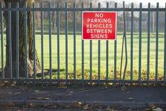 Κανένας χώρος στάθμευσης μεταξύ του κόκκινου σημαδιού σημαδιών στο φράκτη στο δρόμο πάρκων στοκ φωτογραφίες με δικαίωμα ελεύθερης χρήσης